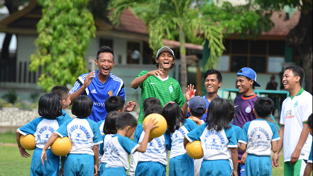 Indonesian Young Coaches haveing fun with a group of children